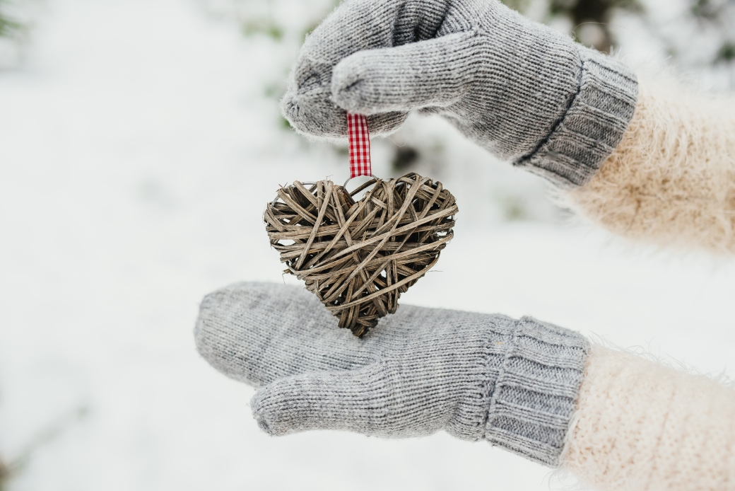 Female hands in knitted mittens with a entwined vintage romantic heart on a snow background. Love and St. Valentine concept.